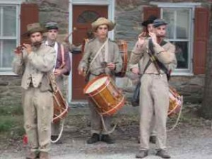 A drum and fife corps performs on the street.