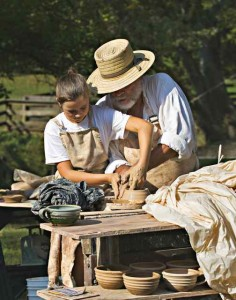 A child gets a hands-on lesson about pottery. Image by Jim Hanna